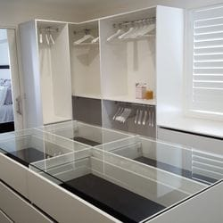 WIR using White HMR Melamine, centre island with 6mm toughened clear glass top. No backing. Open drawer fronts and white 32mm diameter hanging rail