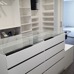 WIR using White HMR Melamine, centre island with 6mm toughened clear glass top. No backing. Open drawer fronts and white 32mm diameter hanging rail. Sloping shoe racks with upstands