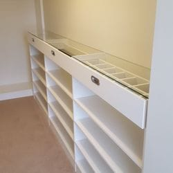 White WIR. Drawer fronts with recessed handle. 6mm toughened clear glass top. Top drawers with dividers. Flat shoe shelving