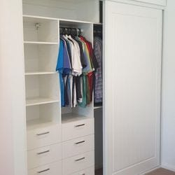 BIR using White HMR Melamine with drawers and shelving behind sliding doors. Above wardrobe storage with profiled hinged doors