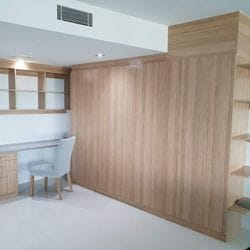 "Study & storage for Q1 apartment. Desk top using Flexipanels ""Concrete"",cabinets using Polytec ""Natural Oak Matt"". Angled shelving to suit tiled floor, bulkhead to suit ceiling line."