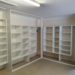 Garage storage using 16mm White HMR Melamine. All suspended 400mm off the floor. Support post for sliding doors to close against. External shoe shelving