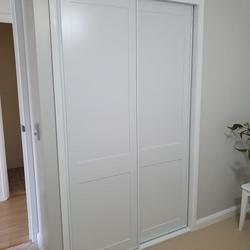 Fully framed shaker profile sliding doors. 2 pack painted finish. Dias White aluminum trims & track