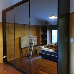 Fully framed 4mm vinyl backed dark grey mirror sliding doors. Dias Black aluminum trims & track
