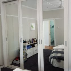 Frame less sliding doors with 100mm 2 pack painted border & mirror glass inserts. Satin Silver recessed handles. Dias Satin Silver top & bottom tracks & 2mm frame