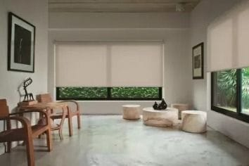 Chain driven standard Quantum Roller blind in translucent fabric in a stoney cream colour