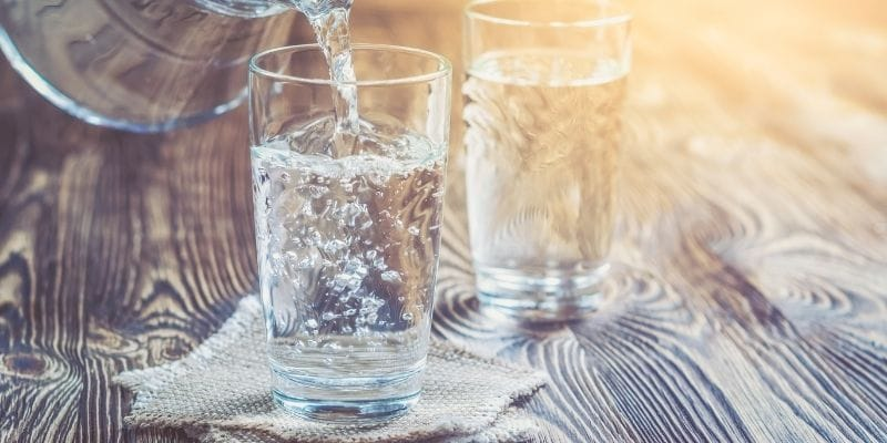 Two glasses being filled with water on a wooden table in the summer sun.