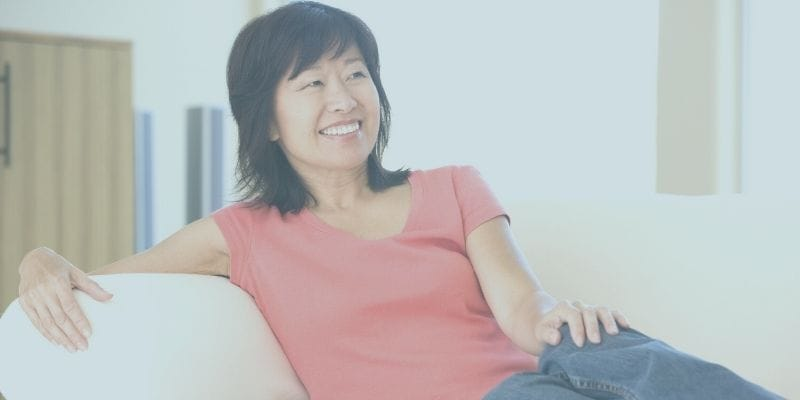 50 year old woman smiling while resting on a couch