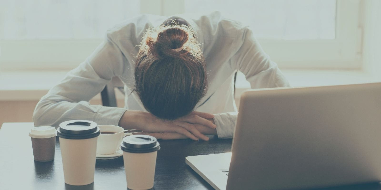 Woman looking tired due to poor sleep habits resting head on desk with coffee cups.