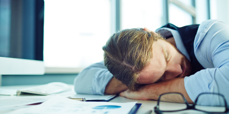 Man experiencing exhaustion due to thyroid or adrenal fatigue and laying on desk