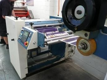 Our high-speed automatic laminator in action. Great for offset and large run digital lamination.