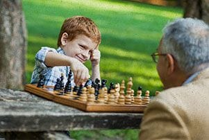 young boy and man playing chess at the park