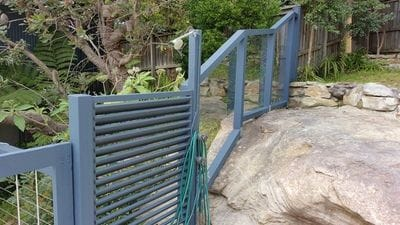 Custom timber frame fence built over sloped rockery, with clear polycarbonate infills