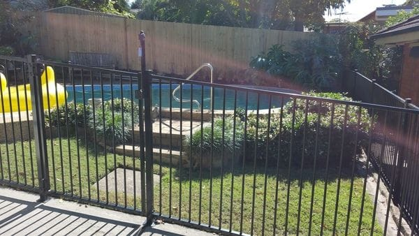 raked-black-tubular-pool-fence---timber-paling-boundary
