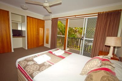 Spacious bedroom with Queen bed and balcony overlooking gardens