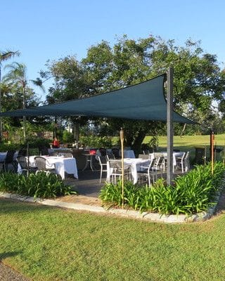 Outdoor dining under a shade sail surrounded by tropical gardens