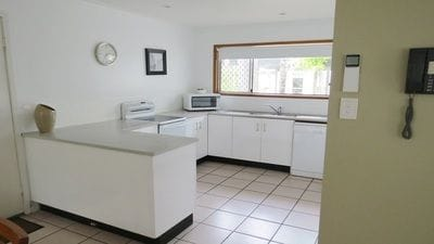 Large corner kitchen with island bench and garden views from the window