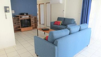 Spacious open plan living room with two sofas and large television.