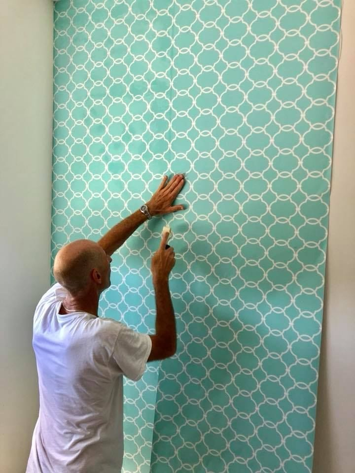 Rod putting wallpaper on bedroom wall