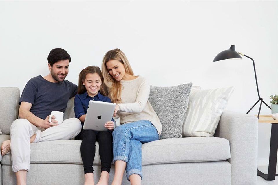 Family sitting on the couch enjoying Customised Air conditioning's Split System Taken Range | Customised Air Conditioning Services and Repairs Perth, Cockburn