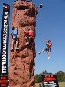 Kids using the climbing wall and abseiling down on an automatic belay system.