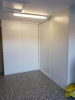 Corner garage storage with white vinyl sliding doors