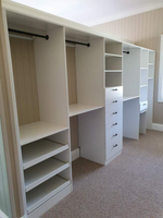 Coastal walk in wardrobe with slide out shoe shelves, black hanging rods and handles.