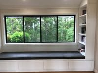 Custom made window seat with wall mounted book shelving