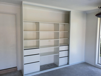 Garage storage with drawers & shelving behind 3 sliding doors on triple track