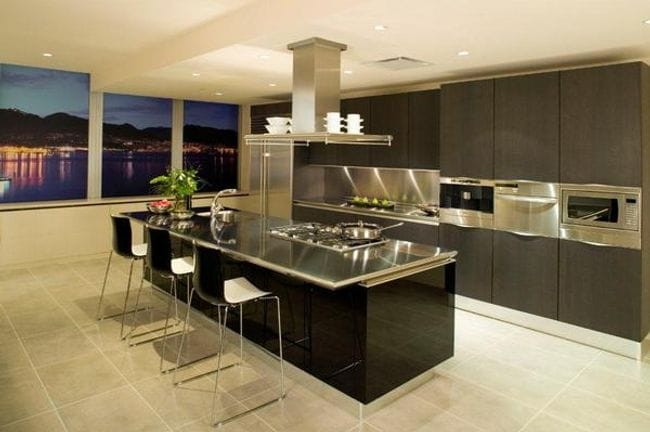 Elegant Kitchen With Stainless Steel Benches And Appliances, Dark  Cupboards, And Tiled Floor.