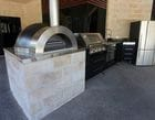 Outdoor kitchen with built-in BBQ and pizza oven servicing the alfresco dining area.