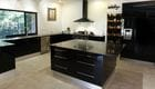 Gloss Black Style-lite Kitchen with integrated fridge. Feature Island Bench. Polished concrete floor.
