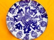 Dancing figures and lucky coin round dinner plate in blue and white