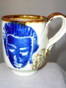 Expresso cup with womans face design in blue and white and iron oxide rim