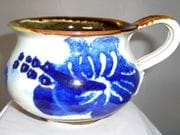 Mug with hibiscus design in blue and white with iron oxide rim