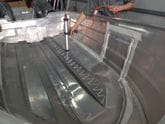Fixtech Fix8 grey being applied to an aluminum hull prior to bonding in a liner